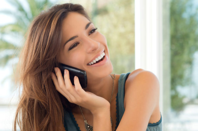 Portrait Of Smiling Beautiful Woman Talking On Mobile Phone